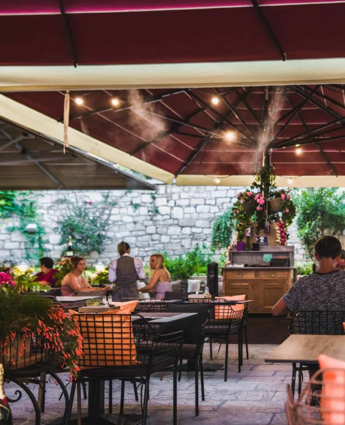 King Krešimir Heritage Hotel outdoor restaurant with flowers and shade in Šibenik old city center