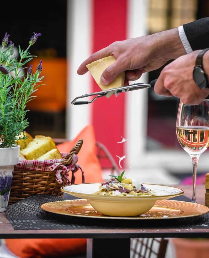 King Krešimir Heritage Hotel restaurant in old city center Šibenik, grated cheese on pasta, tasteful dish and glass of white wine, lavander flower