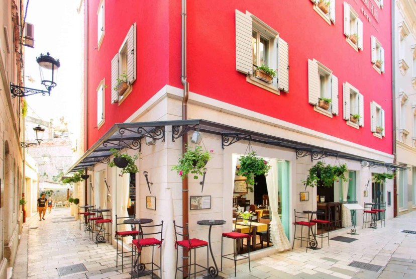 Marmont Heritage hotel in the city center in Split, luxury red hotel on the corner with tall bar stools and flowers