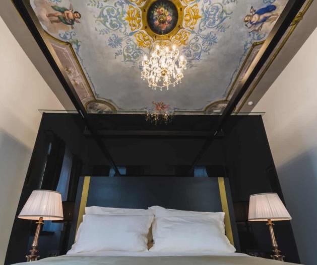 Luxury bed with fresco ceilings and crystal chandelier in Historical Room King Krešimir Heritage hotel, Šibenik