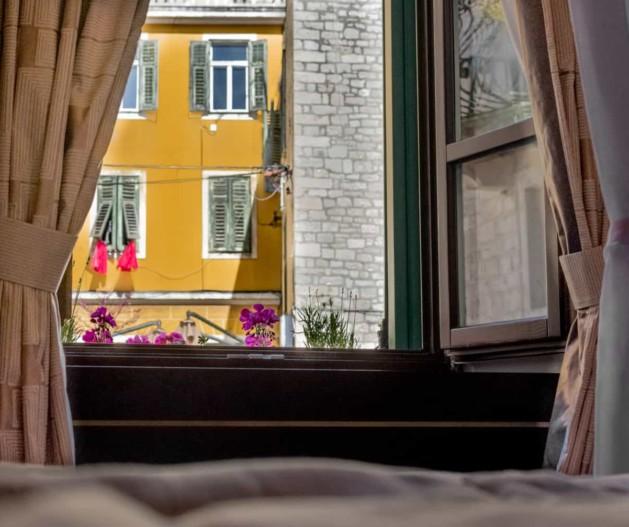 Room view of city Šibenik from wooden window with flowers, King Krešimir Heritage hotel