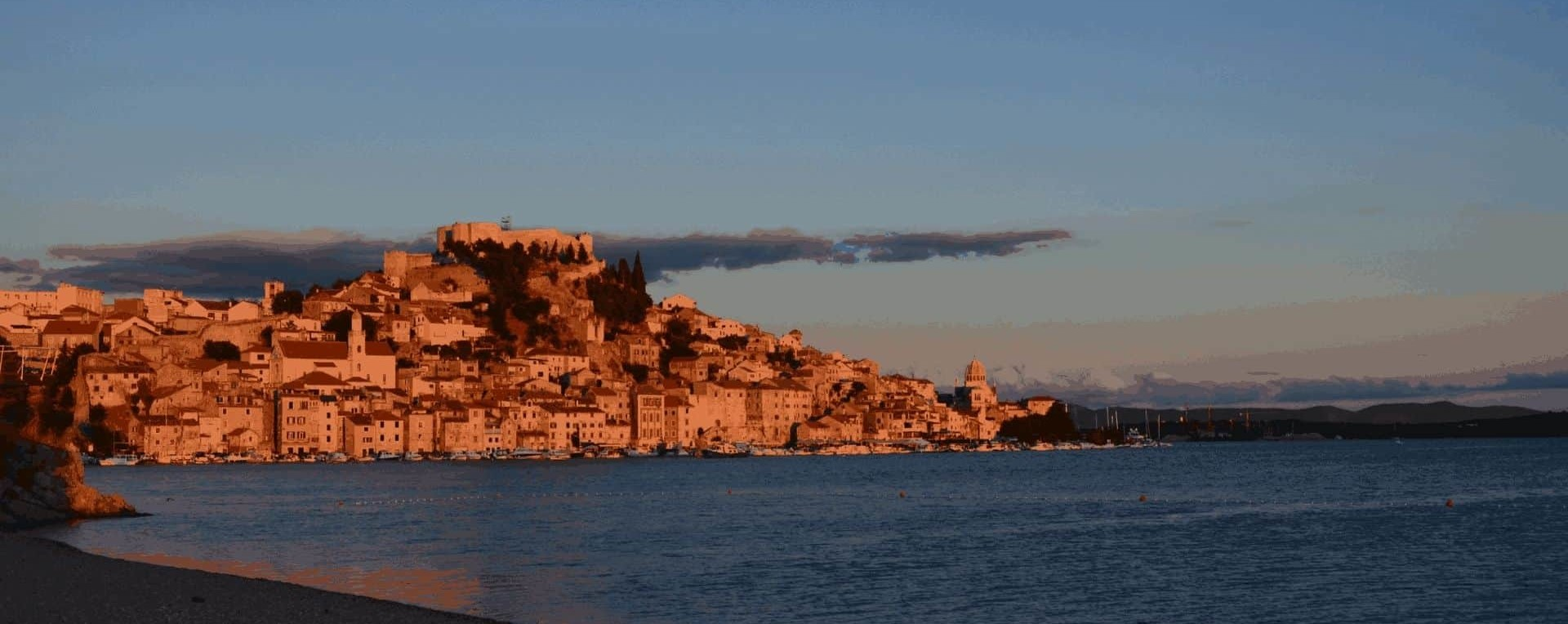 Unique view of the Sibenik old town along with Unesco protected St. James cathedral and St. Michael Fortress from Banj Beach by sunset